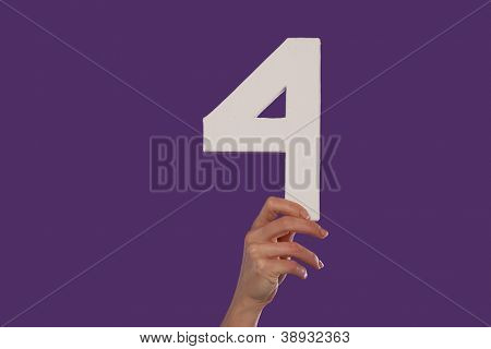Female hand holding up the number 4 against a purple background conceptual of numbers, measurement, amount, quantity, accounting and mathematics