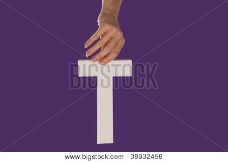 Female hand holding up the uppercase capital letter T isolated against a purple background conceptual of the alphabet, writing, literature and typeface