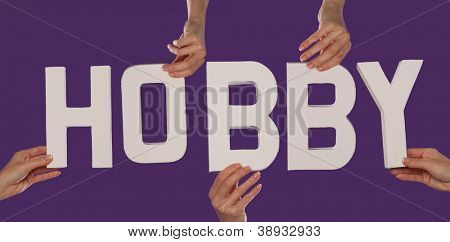 White alphabet lettering spelling HOBBY held up over a purple studio background by outstreched female hands