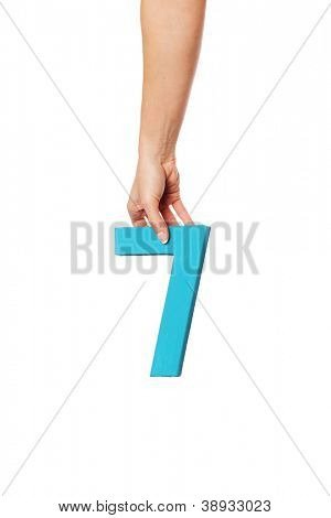 Female hand holding up the number 7 against a white background conceptual of numbers, measurement, amount, quantity, accounting and mathematics