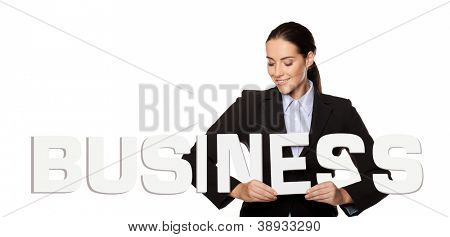 Smiling attractive businesswoman holding the word BUSINESS in white capital letters in her hands isolated on a white background