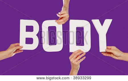 Female hands holding text word for BODY in white capital letters isolated on a purple studio background