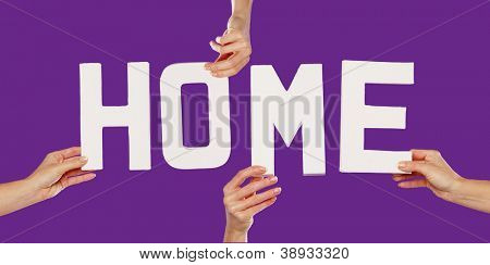 Female hands holding the text word for HOME in white capital letters isolated on a purple studio background