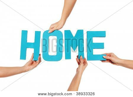Female hands holding text word for HOME in turquoise blue capital letters isolated on a white studio background