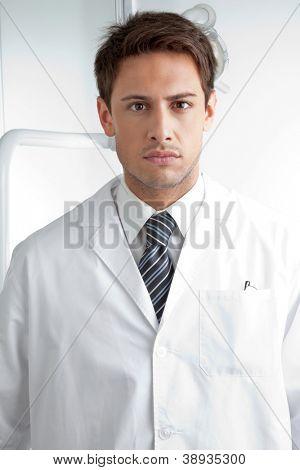 Retrato de grave dentista masculino vestindo examination em clínica