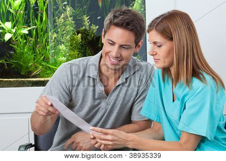 Female dentist showing report to happy male patient in clinic