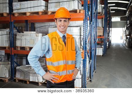 Portrait of confident young supervisor standing at warehouse