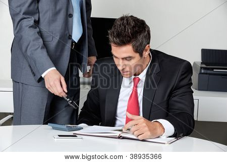 Two businessmen calculating finances at desk in office