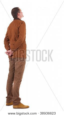Back view of stylishly dressed man in a brown jackett  looking up.   Standing young guy in jeans and  jacket. Rear view people collection.  backside view of person.  Isolated over white background.