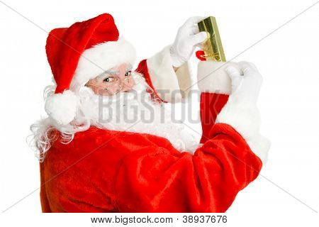 Santa Claus stuffing a christmas stocking.  Isolated on white.