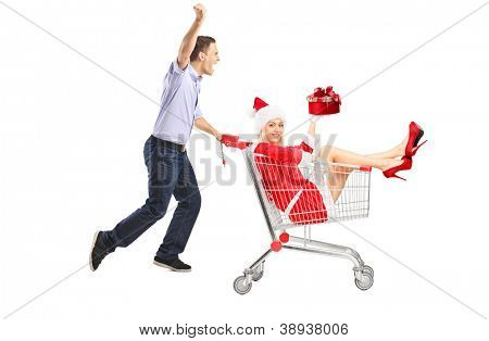 Happy guy pushing a female with gift in a shopping cart isolated on white background