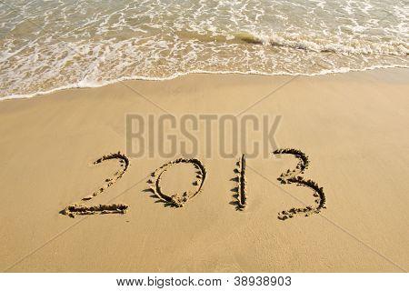 Mão de ano 2013, escrita na areia branca em frente ao mar