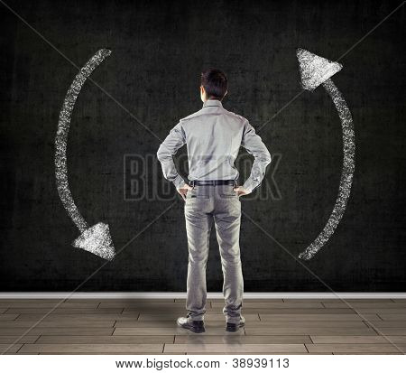 young business man in front of a concrete wall showing two arrows