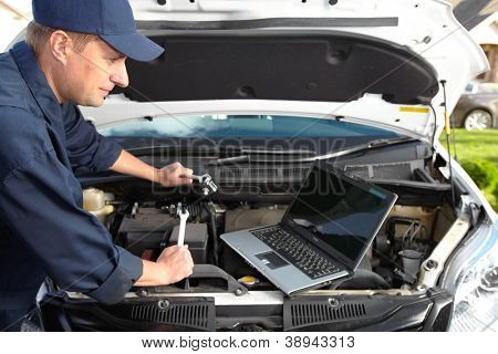 Car mechanic working in auto repair shop.