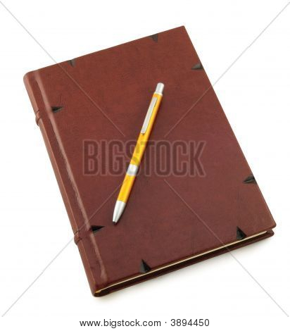 Brown Diary With Yellow Pen In A Center