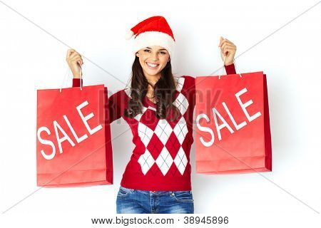 Happy girl in Santa cap holds red paperbags with symbol of sale