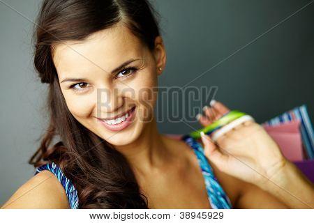 Retrato de morena feliz com paperbags depois das compras