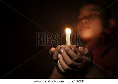 Young novice monk holding a candlelight