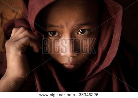 Um monge noviço jovem coberto sua cabeça pelo manto