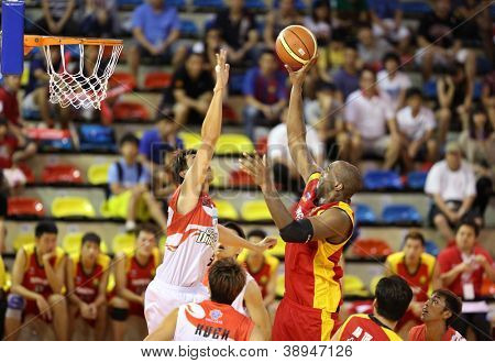 KUALA LUMPUR - OCTOBER 27: Farmcochem's Christopher Garnet (red) shoots over Dragons' Chee Li Wei in a Malaysia National Basketball League match on October 27, 2012 in Kuala Lumpur, Malaysia.