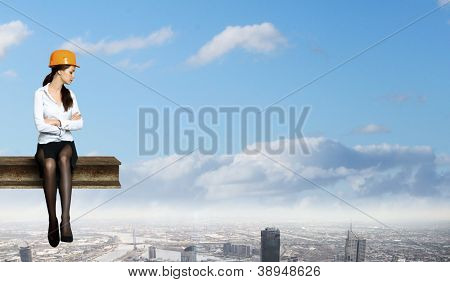 Business woman sitting high over a cityscape