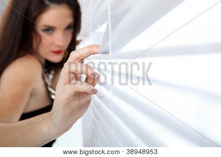 Woman peeking through venetian blinds