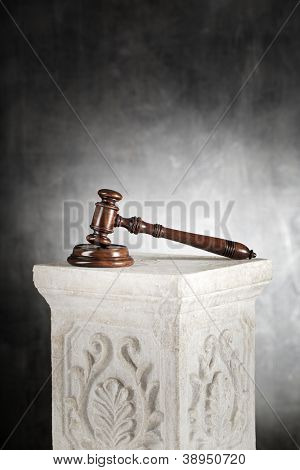 High quality mahogany gavel with sound block on a plaster column.