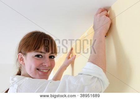 Female decorator hanging wallpaper border