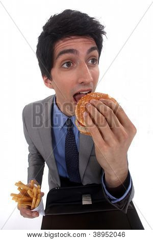 Man eating a hamburger and fries