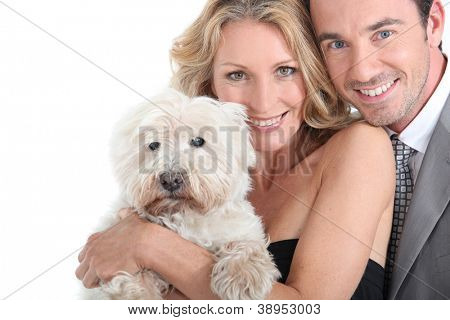 Couple cuddling dog.