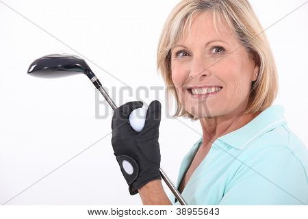 mature blonde woman taking golf club and golf ball