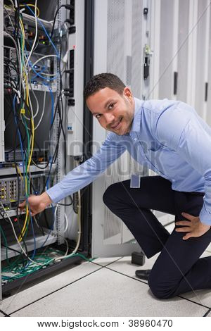 Smiling man adjusting cable in the server in data center