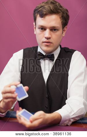 Dealer sitting at table of a casino while shuffling a deck of cards