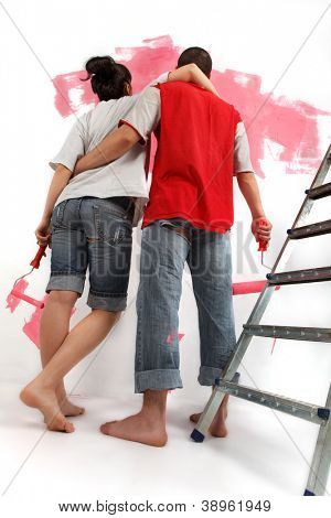 Young couple of workers painting on a wall with roller