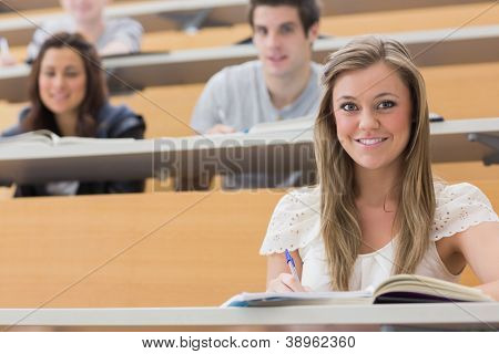 Students sitting at the lecture hall while smiling and taking notes