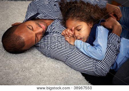 Ethnische Vater und wunderschöne kleine Tochter schlafen am Boden zu Hause