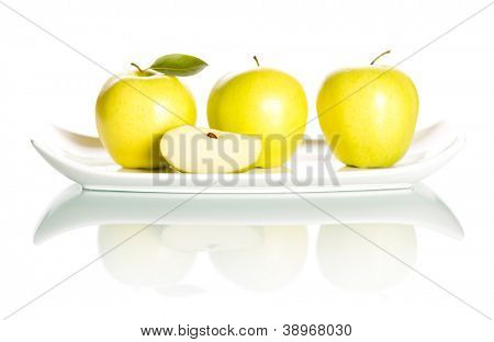 Delicious fresh green apples and slice on elegant plate isolated on white background.