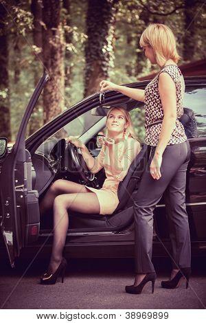 Distribuidor de coche da las llaves de un auto nuevo al cliente principal