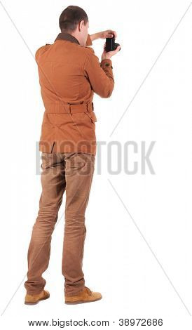 Back view of man photographing.   stylishly dressed in casual clothes photographer. Rear view people collection.  backside view of person.  Isolated over white background.