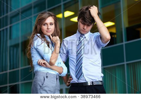 Young worry beautiful businesswoman and handsome businessman in blue shirts, background
