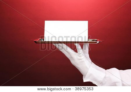 Hand in glove holding silver tray with blank card on red background