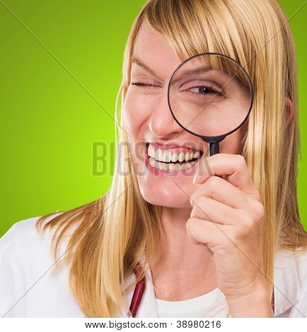 Happy Doctor Looking Through Magnifying Glass against a green background