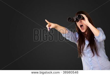 Portrait Of A Young Woman Looking Through Binoculars On Black Background