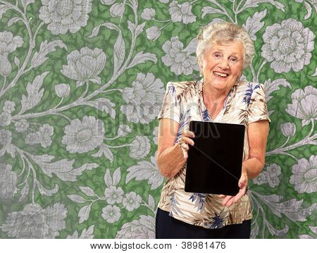 Portrait Of A Senior Woman Holding A Digital Tablet, Indoor