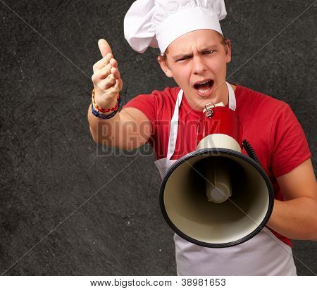 portrait of young cook man screaming with megaphone and gesturing against a grunge wall