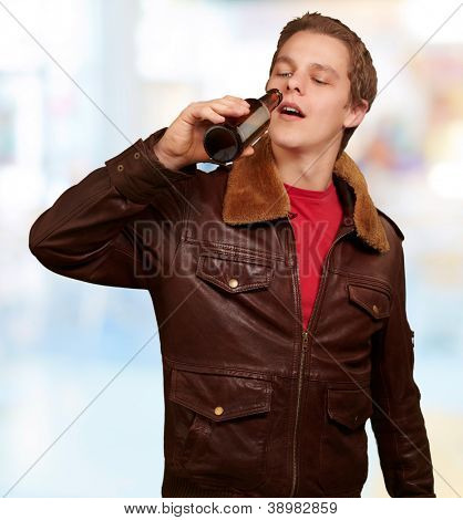 portrait of young man drinking beer indoor