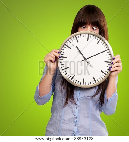 Woman Holding Clock With Squinted Eyes Isolated On Green Background