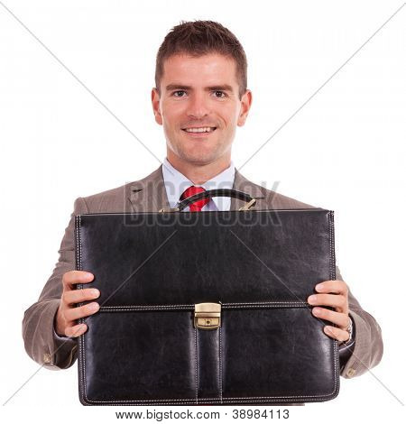 smiling young business man offering a black briefcase over white background