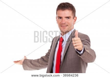 smiling young business man presenting something in the back and showing thumbs up gesture while looking at the camera