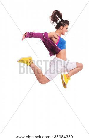 side view of a young woman hip hop dancer jumping with a violent expresion on her face and with arms extended